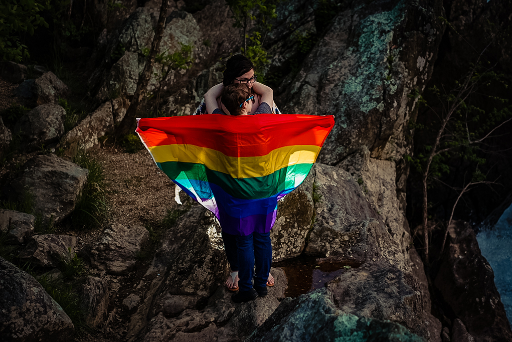 Two brides to be posing with a pride flag during their session at Great Falls by Potok's World Photography, engagement photographers in Maryland