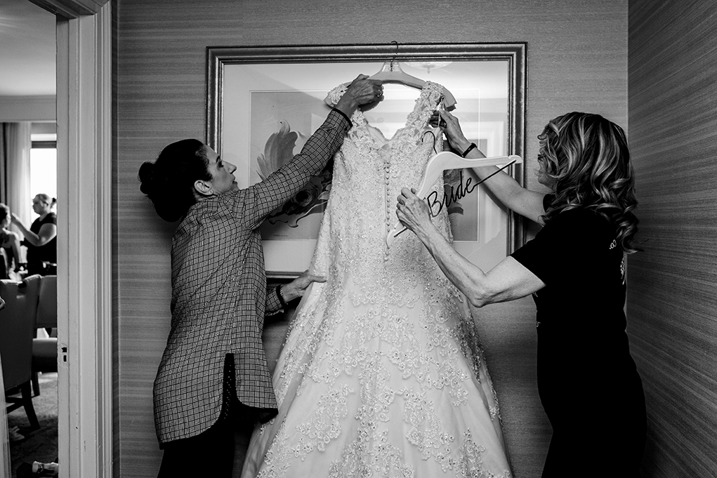 Mother of the bride and aunt hanging wedding dress atOmni Shoreham DC wedding by photographers Potok's World Photography