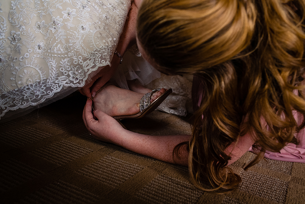 Maid of honor helping bride with shoes atOmni Shoreham DC wedding by DC wedding photographers Potok's World Photography