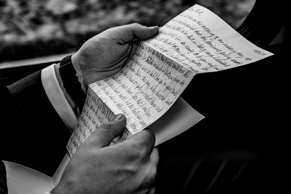 Groom reads letter on bus on the way to wedding ceremony after leaving Omni Shoreham by DC wedding photographers Potok's World Photography