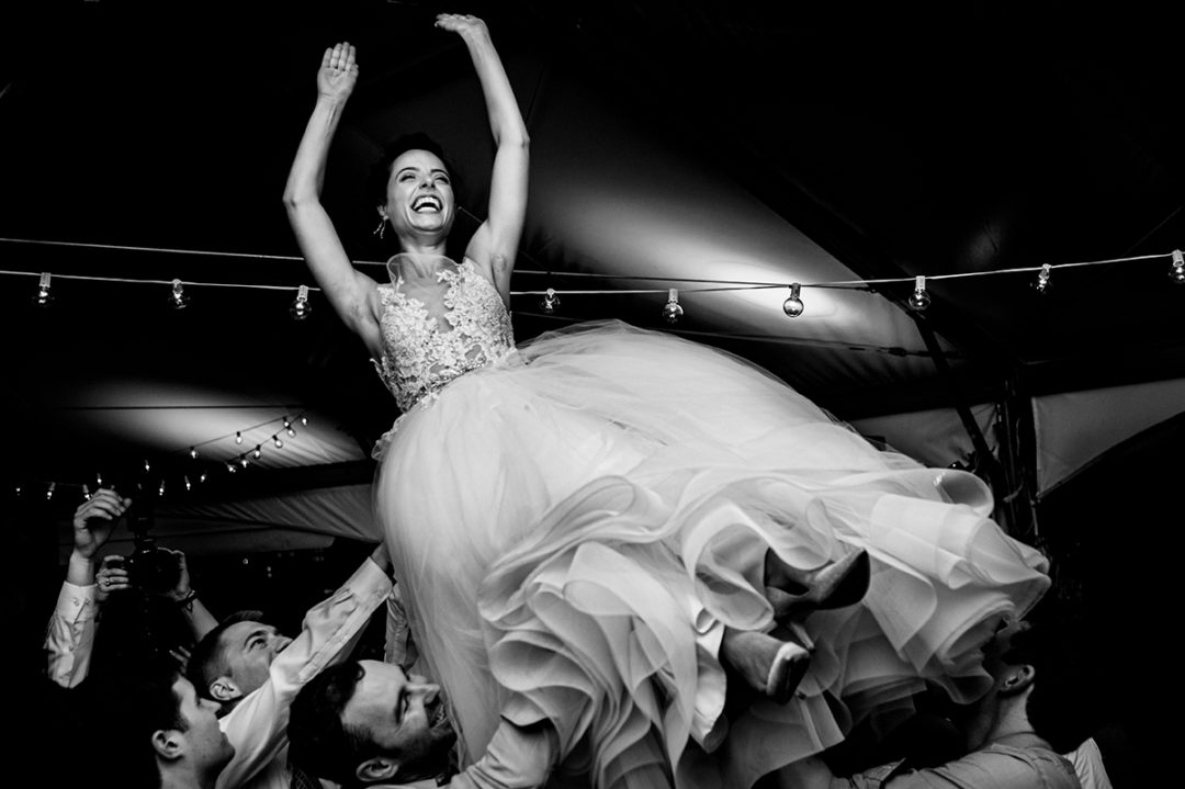 Bride thrown up in the air on dance floor at a wedding reception at 101 Constitution which is one of the best wedding venues in DC by Potok's World Photography