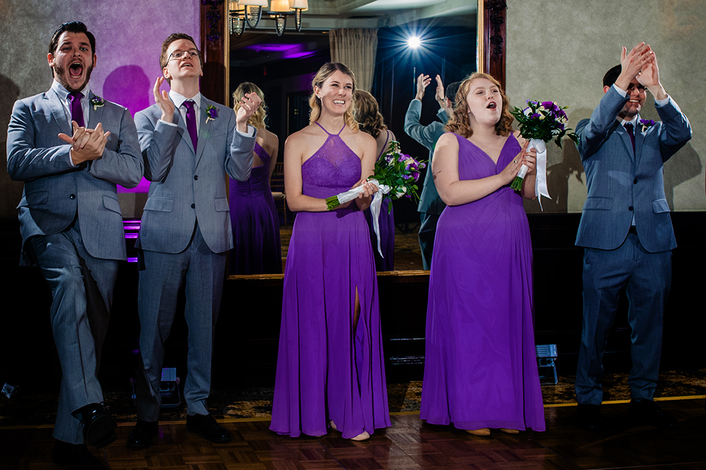 Bridal party cheering brides on as they walk in for their first dance at City Club of Washington by DC wedding photographers Potok's World Photography