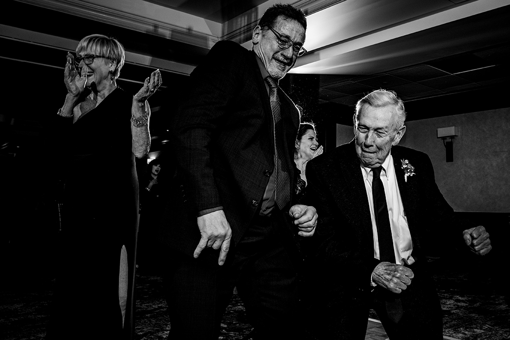 Father of the bride shaking a leg at City Club of Washington reception by DC wedding photographers Anji and Pete Martin of Potok's World Photography