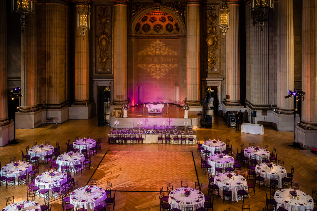 Wedding decor at the Mellow Auditorium with elements of gold, pink and purple. Tall cylinder vases with floating candles add an element of elegance by DC wedding photographers Potok's World Photography