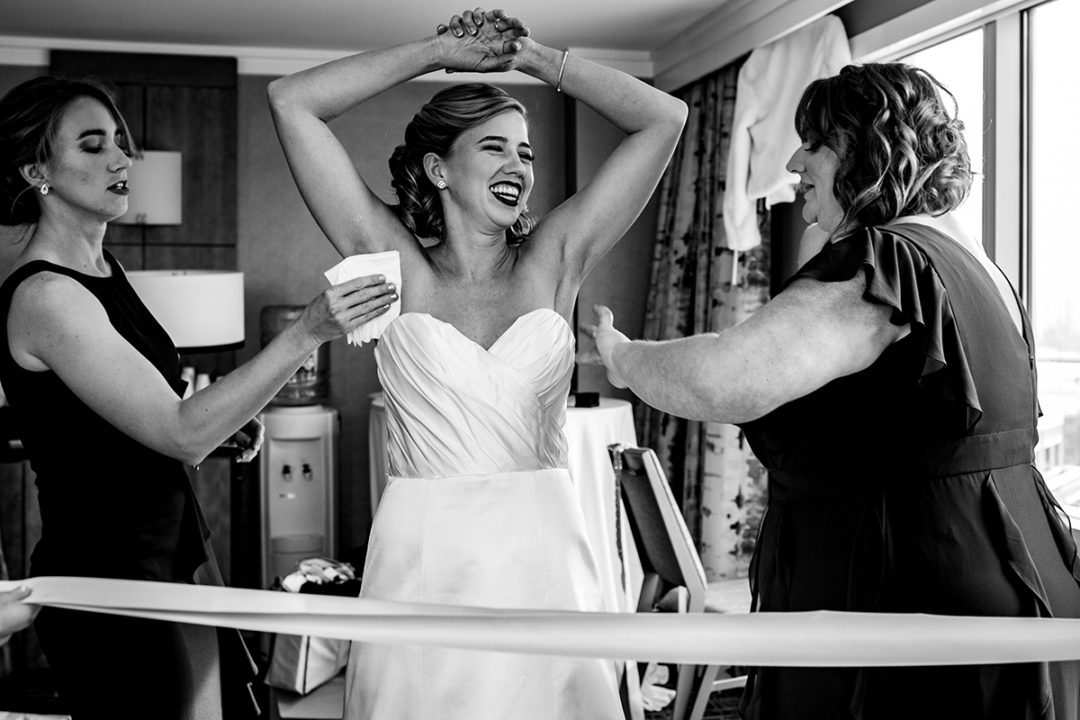 Bride wearing wedding dress and is being helped by her maid of honor at the Westin in Old Town Alexandria by DC wedding photographers of Potok's World Photography