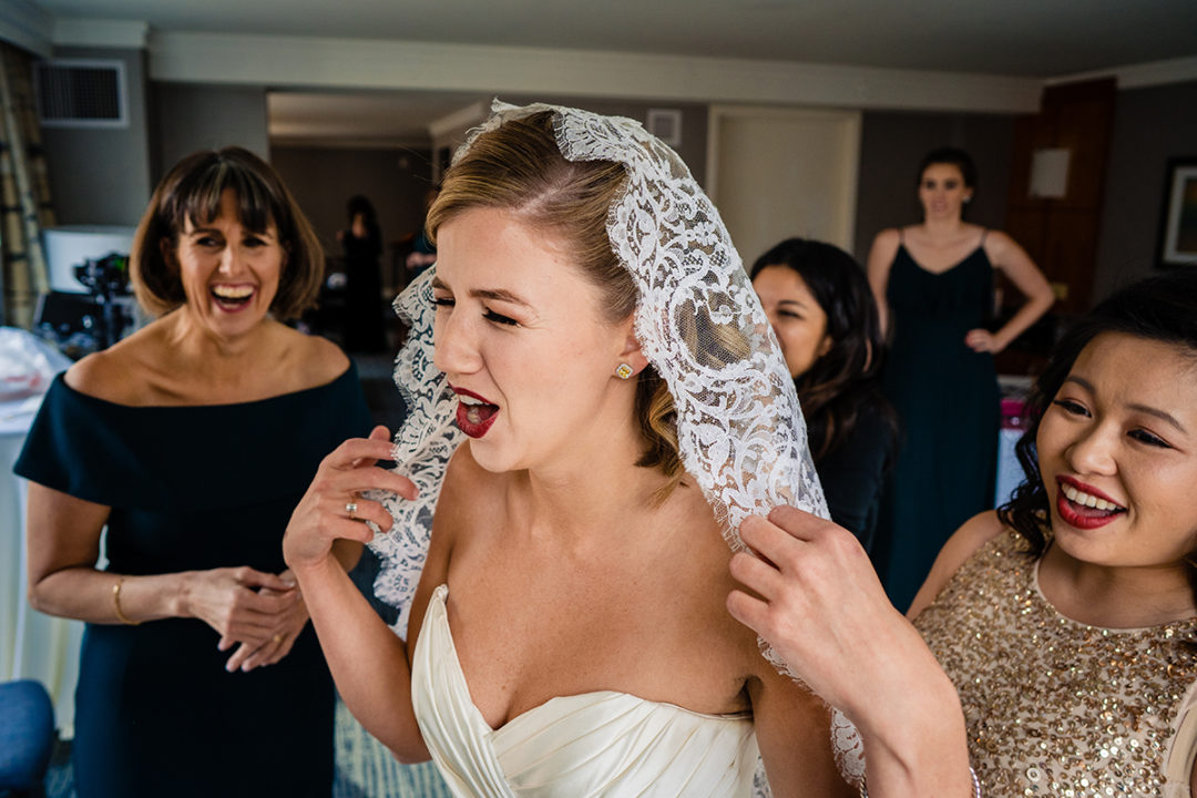 Bride having a moment with her mother and bridesmaid while wearing her grandmother's veil at the Westin in Old Town Alexandria by DC wedding photographer Potok's World Photography