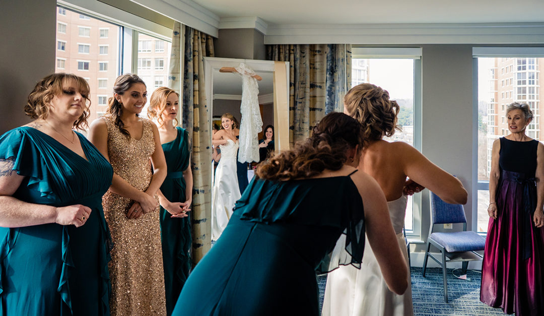 Bride getting into her wedding dress with her bridal party at the Westin Old Town before Carlyle Club Alexandria reception by DC wedding photographers of Potok's World Photography