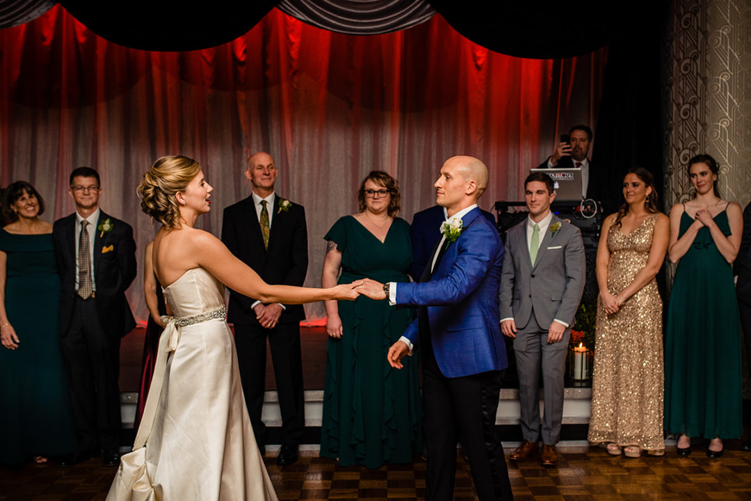 Bride and groom's first dance at their Carlyle Club Alexandria wedding reception with groom's dad and bridal party watching by DC wedding photographers Potok's World Photography