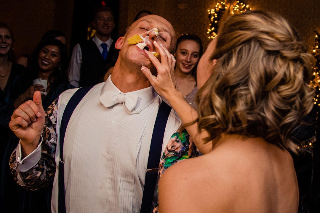 Bride smashes piece of cake during cake cutting at the Carlyle Club Alexandria by DC wedding photographers Potok's World Photography