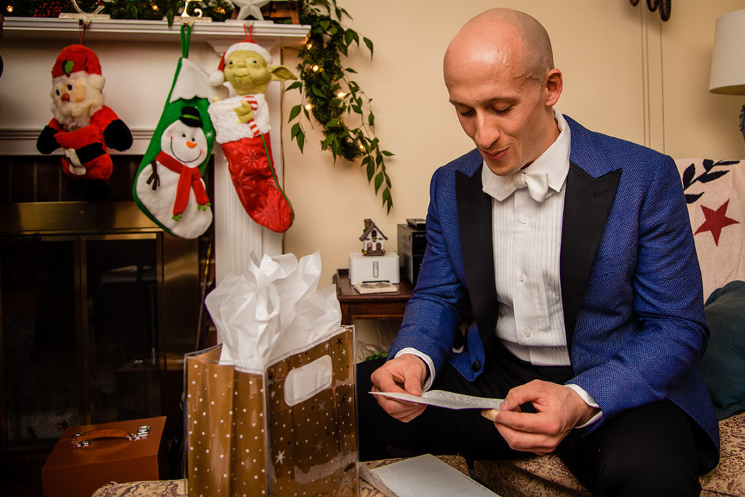 Groom reading letter from bride before their church wedding ceremony and reception at the Carlyle Club Alexandria by DC wedding photographers Potok's World Photography