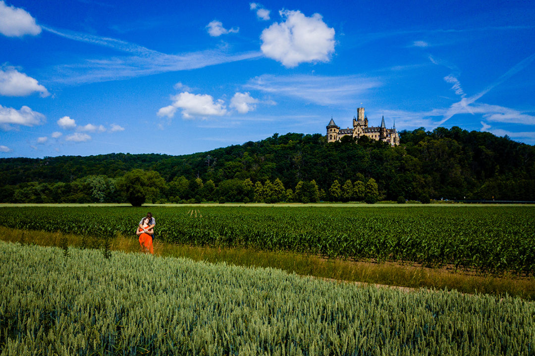 Drone shot of Couple in the fields outside with the castle in the background during Marienburg Castle engagement photos in Germany by Washington DC wedding photographers Potok's World Photography