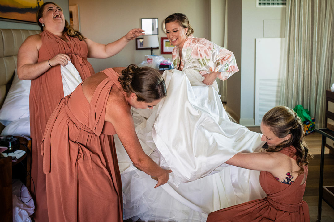 Bride getting into bridal dress with her bridesmaids at Lansdowne Resort and Spa in Leesburg before her Vanish Brewery wedding by DC wedding photographers Potok's World Photography
