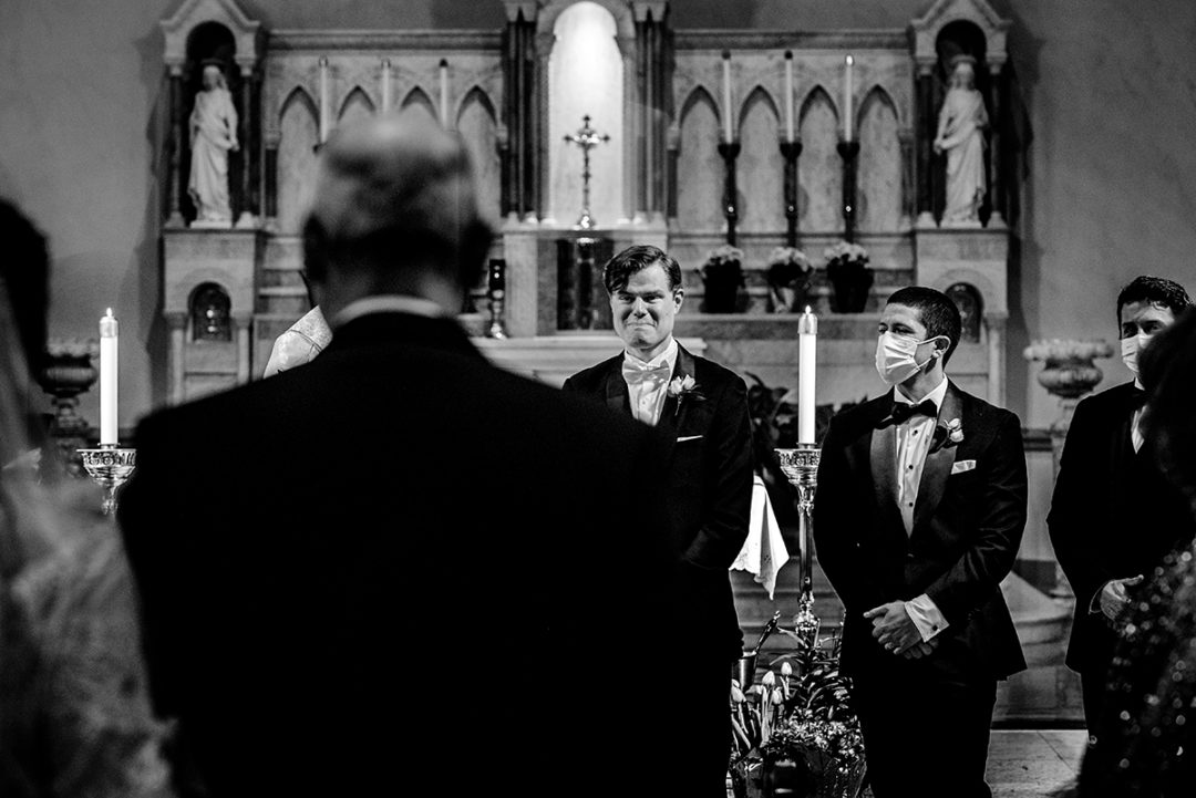 Groom seeing his bride for the first time when she walks down the aisle during their church wedding ceremony in the Nation's Capital by Washington DC wedding photographers of Potok's World Photography